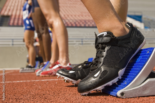 Group of female track athletes on starting blocks, close-up view