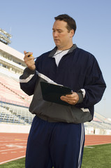 Sports coach looking at stopwatch