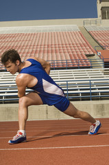 Runner on a track, stretching