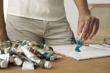 artist squeezing paint onto palette