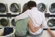 Young couple washing clothes at launderette