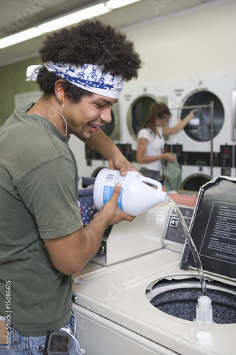 Young man washing clothes at launderette