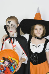 Portrait of girl embracing boy 7-9, wearing Halloween costumes