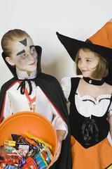 Girl and boy 7-9, wearing Halloween costumes, studio shot