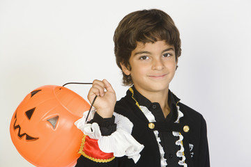 Portrait of boy 7-9 wearing Halloween costume, with jack-o-lantern