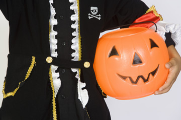 Boy 7-9 wearing Halloween costume, with jack-o-lantern