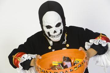 Portrait of boy 7-9 wearing skeleton mask, holding candy bowl