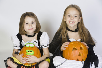 Portrait of girls 7-9 wearing Halloween costumes, with jack-o-lanterns