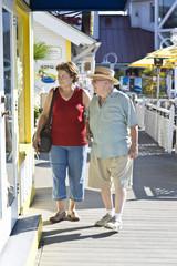 Senior couple on vacations watching window displays