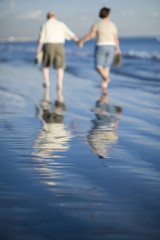 Senior couple walking on beach, reflecting in water