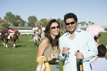 Couple toasting on polo field, portrait