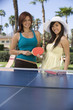Two young women playing table tennis, portrait