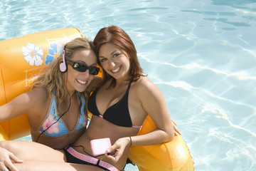 Two Young Women on Inflatable Raft in Pool, Portrait