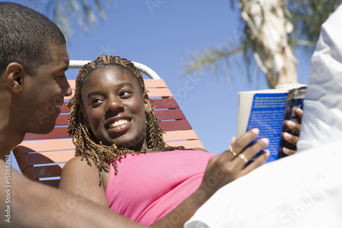 Young Couple Reading Under Palm Tree