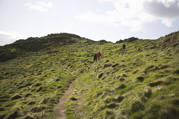 Three adults climbing a hillside