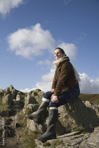 Mature woman sitting on a rock