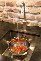 Tomatoes in colander in sink