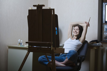 Woman sitting in front of easel, smiling