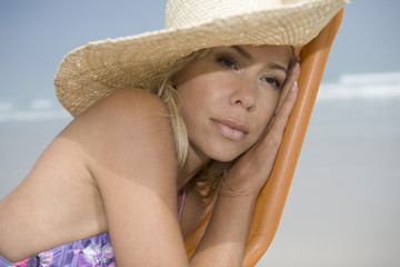 Mid adult woman leaning on deckchair and daydreaming