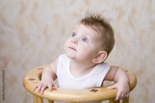 Baby boy sitting on high chair, looking up