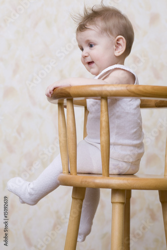 Baby boy sitting on high chair, laughing