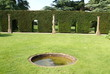 topiary hedge with openings. pond. columns. shape