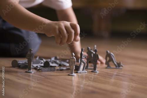 Boy playing with toy soldiers on floor
