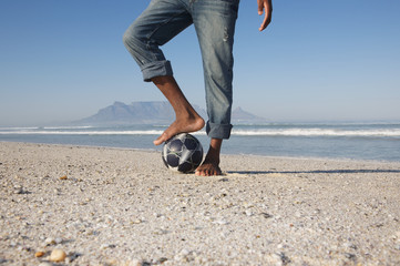 Mans foot on soccer ball, beach scene
