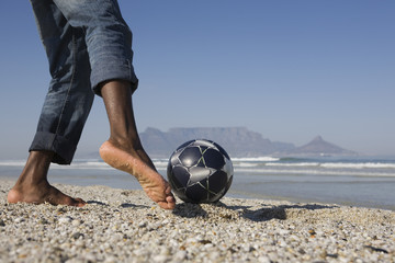 Man playing soccer on beach, low section