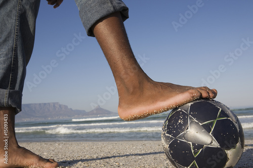 Foot on soccer ball, beach scene
