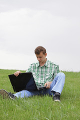 Guy sitting on grass with laptop