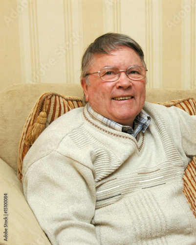 Older Man wearing glasses,smiling, sitting on sofa