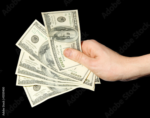 Money in a hand on a black background. (isolated)