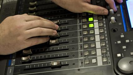 Sound producer behind work. Management of mixer