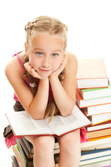 Thoughtful little schoolgirl sitting on a stack of books....
