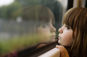 Little girl looking through window
