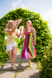 Two happy young women are runing in a park poster