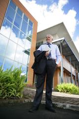 Homme senior avec ordinateur portable devant des immeubles