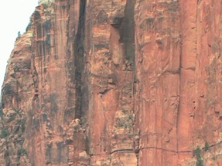 Rock Climbers on a 200 foot rock face in Zion National Park Utah