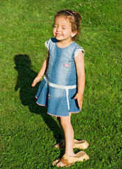Smiling little girl wearing her mother's slip-on