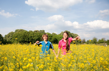 Girl and boy relaxing on meadow full of yellow flowers. Soft foc