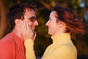Young woman fondles her boyfriend's face with tenderness