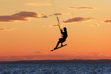 Windsurfer jumping at sea during sunset