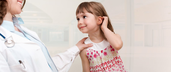 Female smiling doctor examining little girl.Room for text