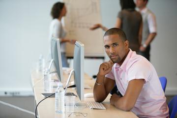 Portrait d'un jeune homme métis assis devant un ordinateur