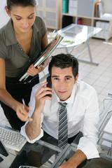 Homme devant un ordinateur près d'une femme avec un micro-casque