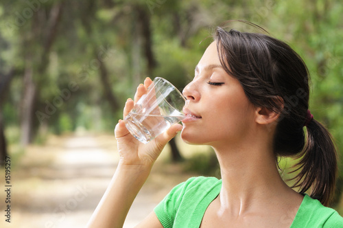 young woman water drinking in glass