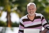 Homme sénior souriant devant un ordinateur portable