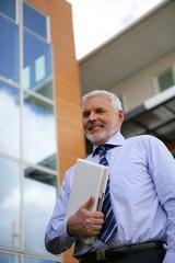 Homme senior en costume avec ordinateur portable sous le bras