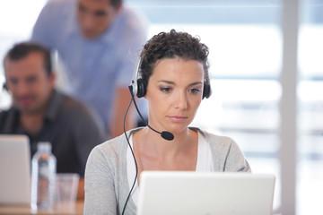 Femme assise devant un ordinateur portable avec un micro-casque